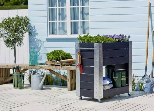 Cubic Hochbeet, dunkles Holz, mit Pflanzen auf Terrasse vor hellblauem Haus