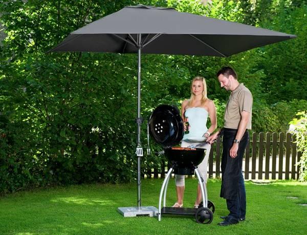 doppler Grill Schirm, junges Paar beim Grillen im Garten unter dem Schirm
